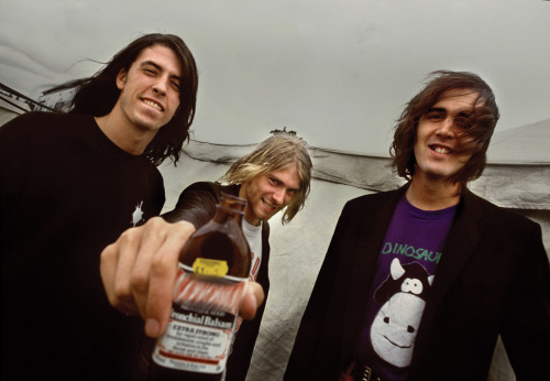 Nirvana at the Reading Festival, 1991 (photo by Steve Gullick). From the New York Times Magazine's What They Were Thinking feature:DAVE GROHL (LEFT): There were 30,000, maybe 35,000 people at Reading. I'm not sure, but it was a lot bigger than any show I had ever played. I think this picture was taken before the gig, and the reason I can tell the difference between pre- and postgig is that Kurt was seriously injured by jumping into my drum set. That bottle he's holding out toward the camera was some kind of incredibly potent cough syrup, and he was carrying that thing around like a flask. So this is preshow, and he was drinking that cough syrup, which led him to dive into my drum set, which put him in a sling for the rest of the night. That gig was definitely a triumph.Read Krist Novoselic's recollection of this moment here.