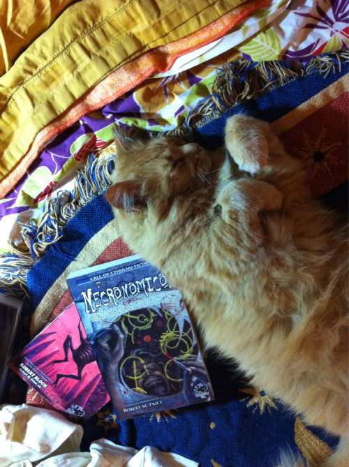 Douglas reclining against The Necronomicon: Selected Stories and Essays Concerning the Blasphemous Tome of the Mad Arab and Mysteries of the Worm: Early Tales of the Cthulhu Mythos.