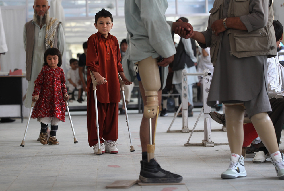 Afghan war amputees and children practice walking  at the International Committee of the Red Cross orthopedic center on  Sept. 10 in Kabul. After more than 30 years of war and a decade since  the 9/11 attacks in the United States, thousands of Afghans, both  military and civilian, continue to pay a heavy price from the conflicts.