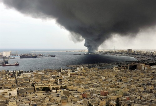 newsflick:  A massive column of smoke fills the sky near Tripoli, reported to be originating from a military warehouse belonging to Gaddafi on Saturday, Sept. 24. A series of explosions rocked the military warehouse and a huge plume of smoke rose over the harbor on Saturday afternoon, although the cause of the blasts is not confirmed. (AP)  Wow, crazy photo right there.