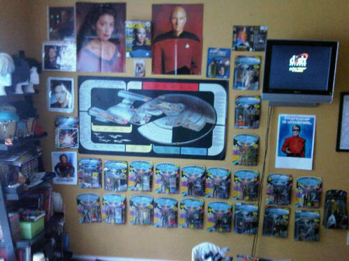 My Star Trek Collection :) (Minus all my Starfleet uniforms, books, soundtracks and trading cards of course) -Posters of Deanna Troi, Picard, and the Starship Enterprise-D -Star Trek TNG Magazine w/ Wesley Crusher on the cover. -22 TNG action figures -1 Star Trek XI action figure of Capt. Pike (BECAUSE I LIKE PIKE.) -Brent Spiner, Wil Wheaton, and John de Lancie's autographs. :) -Star Trek First Contact VHS cover (I own three copies, so why not?) -1983 V poster (It's not trek, but it's in the pictures so I figured I count it. :D) -A picture of Kate Mulgrew -Random pic of Picard as Locutus. My friend was nice enough to let me use her camera so I could show you all.