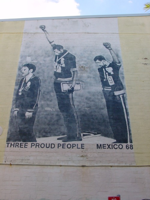 Three Proud People mural, Newtown Sydney Silver medallist Peter Norman from Australia (left), Gold Medallist Tommie Smith, (center) and Bronze medallist John Carlos (right) after the 200m in the 1968 Summer Olympics wearing Olympic Project for Human Rights badges. via &