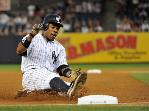 Curtis Granderson of the New York Yankees slides into third base in the bottom of the first inning against the Boston Red Sox on September 25, 2011 at Yankee Stadium in the Bronx borough of New York City. - Photo by Christopher Pasatieri/Getty Images
