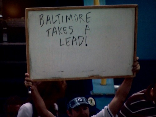 inothernews:  Hahaha, the staff at Tropicana Field refuses to flash the score of the Baltimore / Boston game (until just seconds ago), so a Rays fan resorts to… creative measures to update his fellow Tampa Bay devotees. My question is… where the Hell did he get the Dri-Erase board?  Seriously…who brings a white board to a ball game???