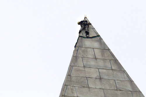 PHOTO OF THE DAY: A man attaches rigging to the top of the Washington Monument on the  National Mall, in Washington, on Tuesday before engineers rappelled down  the sides of the monument to survey the extent of damage sustained to  the monument from the Aug. 23 earthquake. (PHOTO: JACQUELYN MARTIN/AP PHOTO)