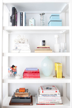 latteetmode:  Fashion Offices with WhoWhatWear Behold the bookshelf of Editorial Director Hillary Kerr! You'll find some of her favorite fashion books, a stash of bright polishes, and some fabulous bookends (the top set are from Polly Blitzer of BeautyBlitz.com, the bottom ones are vintage from Etsy).