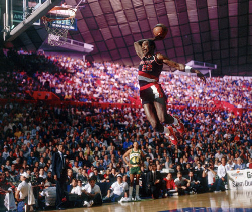 "nbaoffseason:  siphotos:  Portland's Clyde Drexler glides through the air during the 1987 Slam Dunk Contest. Seattle's Terrance Stansbury looks on from the bench. (AP)  ~ Current favorite Tumblr? SI's photo blog. I could spend an entire afternoon looking back at Sports history, through the photos from the SI Vault.   Also, if you ever wondered why Clyde Drexler was nicknamed, ""the Glyde"", here is part of your answer, that photo right there. Amazing."