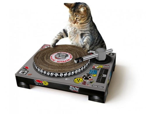 "Turn your kitty into a tiny DJ with this Cat Scratch turntable by SUCK UK! ""Never let it be said SUCK UK don't dabble in science. In the name of completely misunderstanding Schrödinger's work we introduce our newest cat/box combination, the scratch mat! Cats scratch furniture to mark their territory, exercise their muscles and for sheer pleasure. All similar reasons youths mix music, and if we are to cross over both those cultures we'd rather get cats mixing music than teenage boys bringing bedraggled birds back to your doorstep. The decks come flat packed and fold together into a simple structure with poseable tone arm and a top which spins as your cat paws at it – meaning you can sit and giggle in a 'LOOK THE CAT IS DOING HUMAN THINGS' way rather than watch in horror as she shreds your favourite couch into tiny pieces."" [via Design You Trust]"