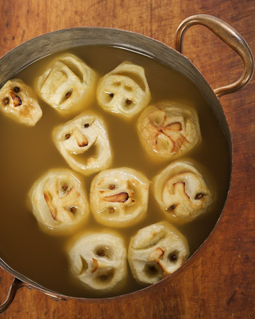 "365daysofhalloween:  Shrunken Heads in Cider Ingredients 2 cups lemon juice 2 tablespoons coarse salt 8 large Granny Smith apples 32 whole cloves 2 gallons apple cider 2 (12-ounce) cans frozen lemonade concentrate, thawed 2 cups spiced rum (optional) Directions 1.Preheat oven to 250 degrees. Line a baking sheet with parchment paper; set aside. In a medium bowl, mix together lemon juice and salt; set aside. 2.Peel apples and cut each in half through the stem; remove seeds and core. Using a sharp paring knife, carve a face, as desired, on the rounded side of each apple half. Place apples in lemon mixture for one minute; transfer to paper towels to drain. 3.Place apples, face-side up on prepared baking sheet and transfer to oven. Let bake until apples are dry and begin to brown around the edges, about 90 minutes. Remove apples from baking sheets and press cloves into the ""eye"" sockets. 4.Combine cider, lemonade, and rum (if using) in a large punchbowl; float shrunken heads on top."