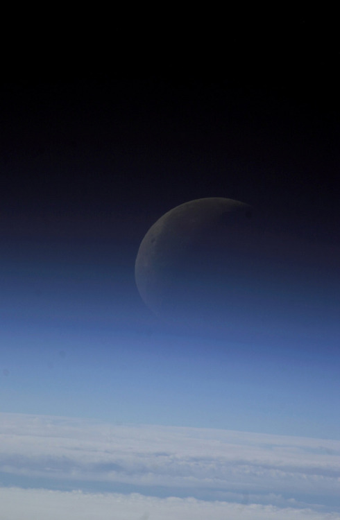 lookhigh:  Ghost moon From a vantage point about 360 km (225 miles) over the Earth, Space Station crewmembers photographed the crescent moon through the upper layers of Earth's atmosphere. At the bottom of the image, a closed deck of clouds is probably at about 6 km (3 miles). The shades of blue grading to black are caused by the scatter of light as it strikes gas molecules of the very low density upper atmosphere. (2003 photo via NASA) HT: Public Domain Images Online