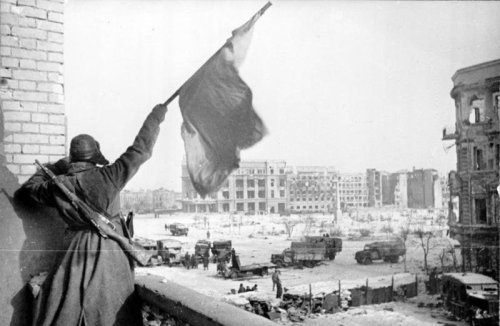 A Soviet soldier waving the USSR over the central plaza within Stalingrad. Early 1943.