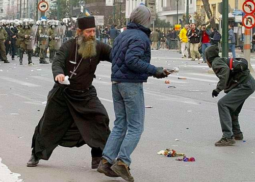 Protests in Greece. Greek Orthodox priest attempts to dissuade protester from throwing a Molotov cocktail at police.