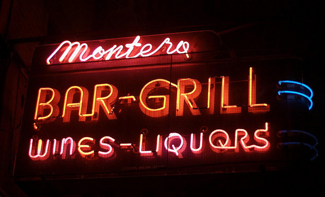 Montero's(in Brooklyn Heights on Atlantic Avenue at Hicks Street) Can you believe it—I had never been inside Montero's until this evening. I can't explain or excuse it, but that's the truth. It's been a rough week. A great week, but exhausting. After seeing my friend Jason's show nearby, I walked over to Montero's for a much needed drink. It's always a little sad to see caged neon, but Montero's sign is wonderful enough I don't mind. It's all simple, single-stroke letters, but with a classic mid-century look. I especially love the taller second L in Grill and the curved capital N in Wines (is there a word for that?) I apologize for using an old photo—the excellent second pair of blue stripes is now working—but the threat of rain and the daily commuting squash made it seem easier to use these photos from January. I'm missing the big photo walks, though. It's been great getting the app together, putting the show up, and fielding all the emails and requests, but I haven't had enough time for photographic wandering. Soon, I hope—my to do list of neon to photograph is long! Thanks to everyone who came to the Project Neon show at the City Reliquary! If you didn't make it yet, it will be up for a while (I'll let you know when I find out the end date), and contrary to what you may have seen elsewhere, they are open Saturday and Sunday from noon to 6p. The Reliquary is a volunteer-run place, so please give a donation if you can. And if you picked up a flyer, you may notice a few mistakes… revised flyers have been placed. There is still one small thing in the show I've yet to change. Did you spot it? It's on the main wall. Welcome to all the many new subscribers! You can also follow along on Flickr and Twitter. If you have an iPhone, download the free Project Neon app (and yes, I am looking into translating it to other platforms). Important news: I'm going to wander Wisconsin's Northwoods for the next week, looking at trees & waterfalls, visiting small taverns, and eating as much cheese as I can manage (believe me, I can manage a LOT of cheese). I will probably be largely out of cell phone range, and at the rate emails have been piling up it may be awhile before I am able to return messages. Please be patient! You may even see a few examples of Wisconsin neon showing up in the old Flickr stream…