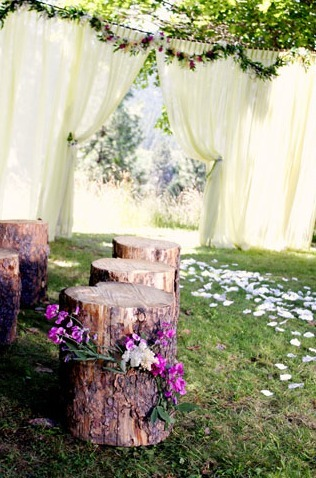 wildernessandweddings:  Such an easy way to set up a backyard wedding: a rope across two trees and hang a flowy curtain overtop. Decorate with wildflowers….AND OH MY the best…LOG CHAIRS. Beautifully simple, easy, elegant, and outdoorsy. Approved!
