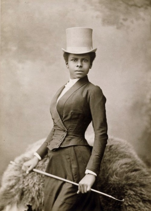 hatsfromhistory:  carolathhabsburg:  Beauty in riding habits. Late 1880s  She is exquisite!  Riding habits were constructed with a feminine silhouette, but were given such masculine details as buttons, cuffs and jacket lapels.  A formal men's hat, such as the top hat shown here, was worn in Victorian times (and later) - sometimes with a veil on the back. The tradition of menswear in riding habits is an old one.  In 1666, a young Samuel Pepys wrote: Walking in the galleries at White Hall, I find the Ladies of Honour dressed in their riding garbs, with coats and doublets with deep skirts, just, for all the world, like mine; and buttoned their doublets up to the breast, with periwigs under their hats; so that, only for a long petticoat dragging under their men's coats, nobody could take them for women in any point whatever; which was an odde sight, and a sight did not please me. They were often trained or longer on one side of the skirt so as to protect modesty while riding sidesaddle.