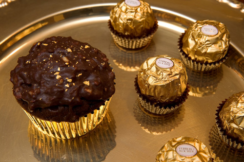 thecakebar:  Ferrero Rocher Cupcake Recipe! I don't have anything else to say! ENJOY! ~~~~~~~~~~~~~~~~~~~~~~~~~~~ Recipe: The cupcake recipe came from Laura of Sweets Made Here. It is for 12 cupcakes. I doubled it. 1/2 c boiling water 6 T unsweetened cocoa powder 1/4 c milk 1/2 t vanilla extract 1 T hazelnut extract 1/2 c unsalted butter, softened 10 T dark brown sugar 6 T granulated sugar 2 large eggs 1 c all-purpose flour 1/2 + 1/8 t baking soda 1/4 t salt In a bowl, whisk the boiling water into cocoa until smooth and whisk in milk, vanilla, and hazelnut extracts. In a large bowl, beat together butter and sugars until light and fluffy, about 2 to 3 minutes, and beat in eggs, 1 at a time, beating well after each addition. Into another bowl, sift together flour, baking soda, and salt and add to egg mixture in batches alternately with cocoa mixture, beginning and ending with flour mixture, and beating well after each addition. Fill each wrapper slightly more than 1/2 way. They will rise a lot. Bake in a preheated 350F oven for about 18 minutes. Cool on a wire rack.Recipe continues here! Need more help? Contact me @thecakebar I love to help!