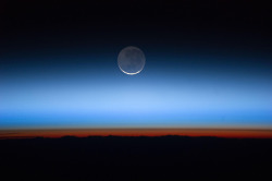 Earth's Moon  Photographed  by the Expedition 28 crew aboard the International Space Station, this  image shows the moon, the Earth's only natural satellite, at center with  the limb of Earth near the bottom transitioning into the orange-colored  troposphere, the lowest and most dense portion of the Earth's  atmosphere. The troposphere ends abruptly at the tropopause, which  appears in the image as the sharp boundary between the orange- and  blue-colored atmosphere. The silvery-blue noctilucent clouds extend far  above the Earth's troposphere. Image Credit: NASA