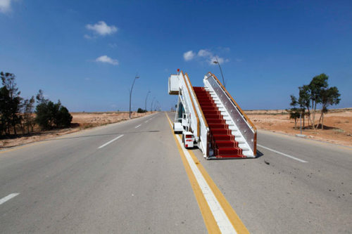 inothernews:  ON THE NEXT ARRESTED DEVELOPMENT   An abandoned VIP stairway is seen on a road at the airport in Sirte,  one of two remaining bastions of support for the deposed Muammar Gadhafi, which is now under the control of anti-Gaddafi fighters.   (Photo: Anis Mili / Reuters via the Telegraph)
