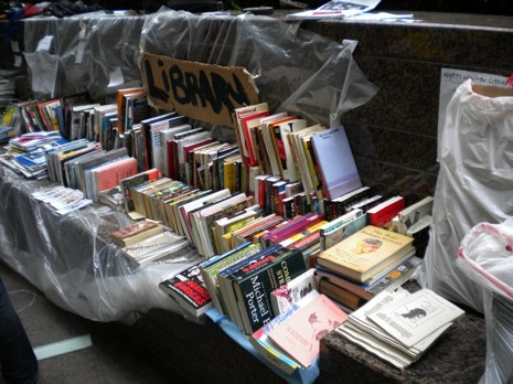"utnereader:  (via The Book Bench)  The morning of day twelve of the Occupy Wall Street protest, a few people are waving signs and shouting slogans. Mostly,  though, everyone is just hanging out. They take naps, play board games,  and pick up books from the haphazardly organized library that occupies a  bench on the side of Zuccotti Park. There is no rhyme or reason to the  selection: a volume of Walter Benjamin's writing sits beside Curtis  Sittenfeld's ""Prep""; the only books that are sectioned off are the  children's books. All together, about one hundred titles—along with back  issues of Harper's—await protesters and passersby—in the spirit of the affair, you needn't be an ""insider"" to borrow.   Intense."