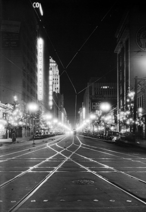 usclibraries:  Downtown Los Angeles at night, circa 1930s. View is of Broadway, looking north from Olympic. Visible on the left side of the street is a sign for the United Artists Theater. Behind the theater are the Texaco and Eastern Columbia buildings.  Bring the streetcars back to L.A.! That's what I say!