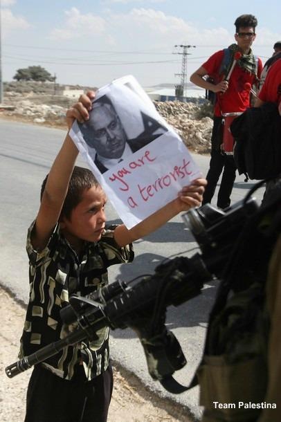 Palestinian boy shows an Israeli soldier a portrait of Israeli Prime Minister Benjamin Netanyahu with writing below it in English which reads 'You are a terrorist' during a protest in the West Bank village of Maasarah on September 30, 2011 in support of thousands of Palestinian prisoners held in Israeli jails, who are on a hunger strike.    thepalestineyoudontknow: