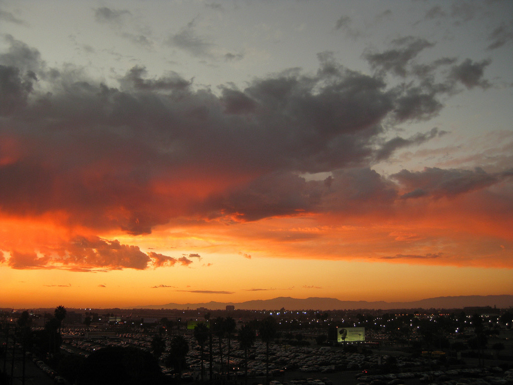Orange sunset over LAX. The Santa Monica mountains are visible as silhouettes in the distance.