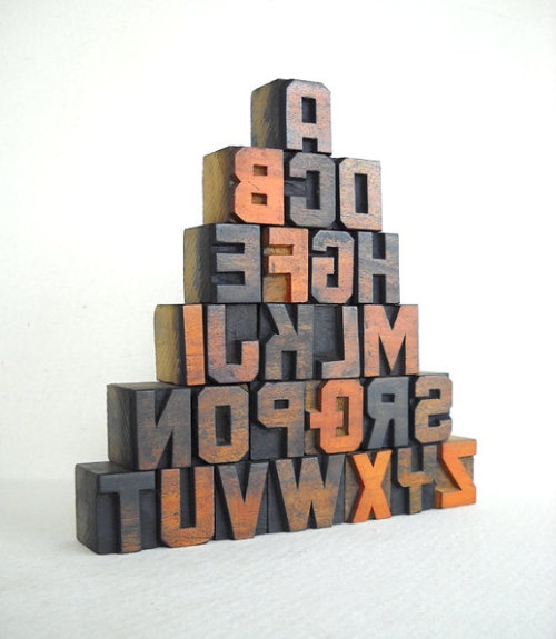 A collection of 26 wooden letters of different fonts and sizes from A to Z