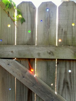 homemadecrap:  Garden Art: Marbles in the fence…. (via Garden Drama) Such a simple idea, but I think our neighbors kids would try to pop them out :(