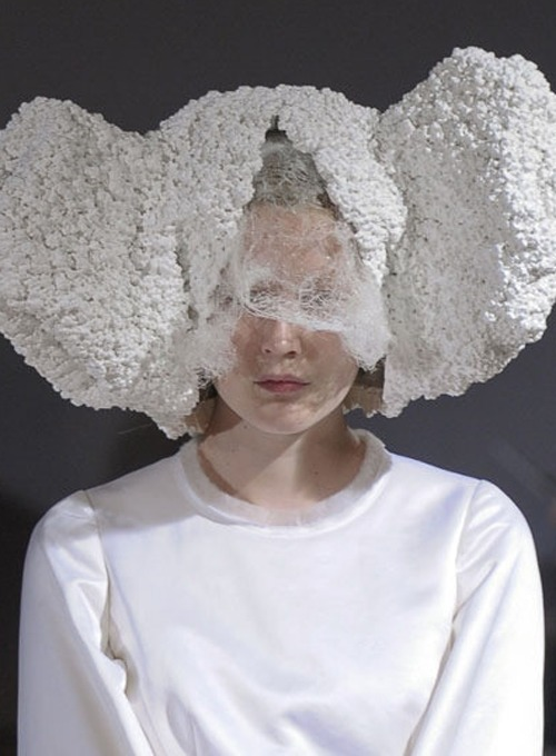 "Comme des Garçons Spring 2012 ""White drama"" ""White drama"" was a precise summation of a show that felt like it tracked a progression through life's dramatic way stations: birth, marriage, death, transcendence. Tradition drapes each of those moments in white and attaches distinct rituals to them, which set off some fascinating echoes in Kawakubo's all-white collection. Some were as obvious as the duchesse satin of a wedding dress or the lace of a christening gown; others were more oblique, such as a reference to a body laid out in white flowers, or the pointy-headed robes worn by church dignitaries during Seville's Semana Santa. The ceremonial grandeur of the clothes and the stately way they were shown felt like yet another echo of the fifties/sixties couture influence that has insinuated itself into Spring 2012. More specifically, there was the spirit of Cristobal Balenciaga, a deeply religious man who elevated the craft of couture to the level of spiritual quest. He believed he could find salvation in the perfect sleeve. It was probably coincidence that sleeves were the signal detail of the Comme collection (they were long and wide, falling almost to the floor), just as it was probably coincidence that the show took place in a Salvation Army building. Unless, of course, you believe there is no such thing as coincidence, a conclusion that was easy to reach given the presentation's inescapable spiritual dimension. It was tempting to see in that a response by Kawakubo to the disasters that afflicted Japan this year, with life-and-death dramas still being played out every day. But that sounds unduly solemn for a show that, for all its grand theme, was still spiked by drollness in details such as the headgear contributed by three different artists, the Westwood hoops, and the lacy lingerie trims that introduced hints of carnality. Yes, the white boots might be worn by technicians in a nuclear reactor. But equally, they could be sixties couture a-go-go.""[style]"