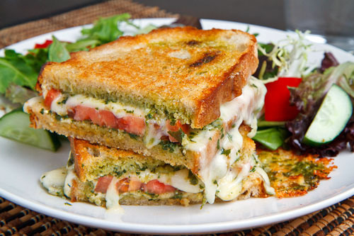 hellyeahrecipes:  Caprese Grilled Cheese Sandwich 4 slices bread  1 large ripe tomato, room temperature, sliced 1/4 inch thick  1 ball fresh mozzarella, room temperature, sliced 1/4 inch thick  4 tablespoons basil pesto  pepper to taste  2 tablespoons olive oil Assemble sandwich and grill until golden brown and the cheese has melted, about 2-3 minutes per side.