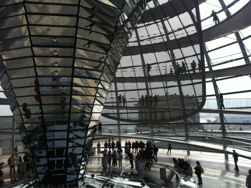 Reichstag, Bundestag Chamber, German parliament lit naturally by indirect reflected  light  off inverted cone of mirrors. Note the massive curved screen that tracks  the sun to prevent direct solar reflection into chamber which would be too  glary.