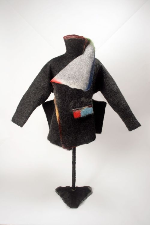 "Jorie Johnson (Joi Rae): Olympia Series Jacket 2006, wool, leather. Photo by Kobayashi You.I love making asymmetrical collars and also working the edge of a piece to produce a soft ""washi"" paper effect rather than a hard cut edge. Here also, the bits of color were laid between the black wool base and the white top layer before the felting process began to help emphasize the collars and jacket edges. My influence came from the Central Asian nomadic herders coats but with a little Joi Rae Textiles twist. Stitched pocket flap and felt rope closure. / Keiko Gallery - Japanese artists"