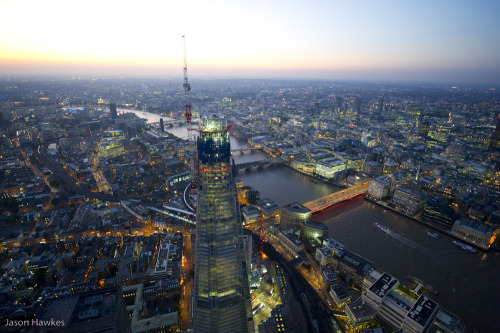 'above The Shard of Glass' Another recent photograph from a helicopter above London at sunset by photographer Jason Hawkes. Here's his shot north west from above London Bridge station taking in, The Shard of Glass nearing completion (bottom centre), the River Thames (diagonal) London Bridge, Canon Street Bridge, Blackfriars Bridge, Millennium Bridge (bottom to top of river), Tate Modern art gallery (left of top of Shard), St. Pauls Cathedral (right of top of Shard), Barbican towers (further right of top of Shard), and… The Tallest Crane in Europe (at the top of the Shard) London: You Are Beautiful