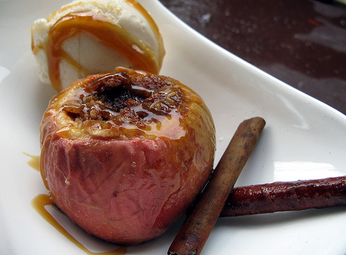 Nut stuffed Baked Apple with Caramel SauceLots of fresh cinnamon and nutmeg, warm apple, cool vanilla ice cream all drizzled with caramel.  Seasonal! CC image via flickr user QuintanaRoo.