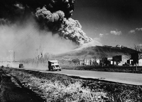 US Army Jeeps driving by Mount Vesuvius during an eruption. Bay of Naples, Italy - March, 1944.