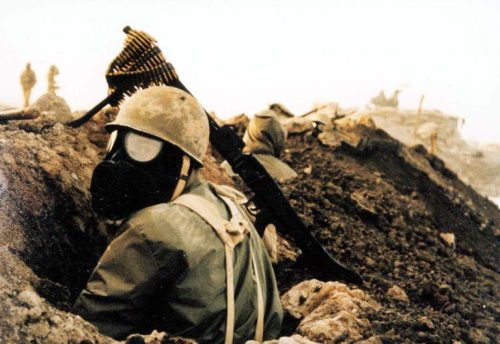 An Iranian soldier wearing a gas mask in a trench during the Iran-Iraq War.