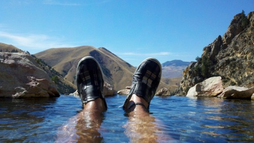 The Plaid Shoes AdventuresGoldbug HotSprings, Idaho 9/23/2011 The moon's glow melted into the horizon as the sun painted the sky with rosehips and calendula. Autumn's harvest. I wiped the frost from my brow and laughed at the frozen clothes still clinging to the picnic bench from last night's adventure in the Challis Hot Springs. We shook the cold from our bones and defrosted our thoughts with the hopes of cowboy coffee as we packed our cottonwood smoke-filled sleeping bags into the oversized – but comfortable - truck. Our 8 mm memories of sleeping under the diamond sea of the Idaho night replaying to the soundtrack of the breaking dawn guided us through the mountains to the trailhead of Goldbug Hot Springs. A lemon sage scented day hike warmed our bodies as the sun gently laid its blanket over the crisp morning.  Mesmerized by the game trails blazing their way through the strata of the ancient wild sagebrush, we entered the craggy canyon with dreams of the hot soaks and lush undergrowth at the end of our uphill battle. We challenged the ever shifting shards of rock biting our feet - the final stone dragons protecting the treasure at the top of the slope.  Out of breathe, but filled with spirit, we reached our green oasis. Clad only in our birthday suits and plaid shoes, we reveled in the hot waterfalls and steamy soaks of the tumbling geothermal stream - nourishing our minds and bodies in that single repleting moment of peace.