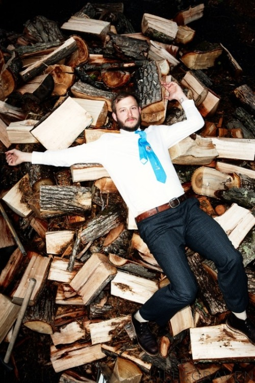 Justin Vernon laying uncomfortably on a pile of logs.