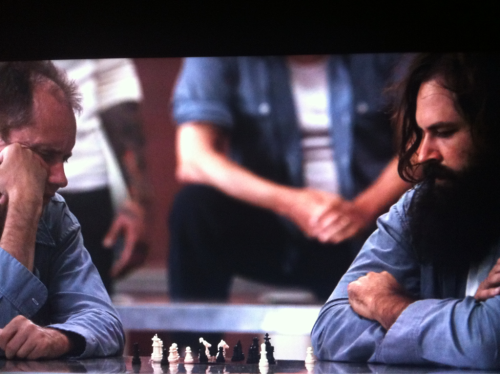 This can't be good…it's Chuck's second scene, this time playing chess. Hope there isn't a third scene. Everyone knows that they always kill the guy with the beard at the end.