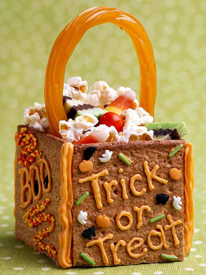 Ready-To-Eat Treat Bag ~ This edible treat bag makes a fun table decoration or take-home gift for a Halloween party. Frosting holds together a graham cracker base and licorice handle. Decorate with piped writing, and fill with popcorn, candy corn and other snacks.