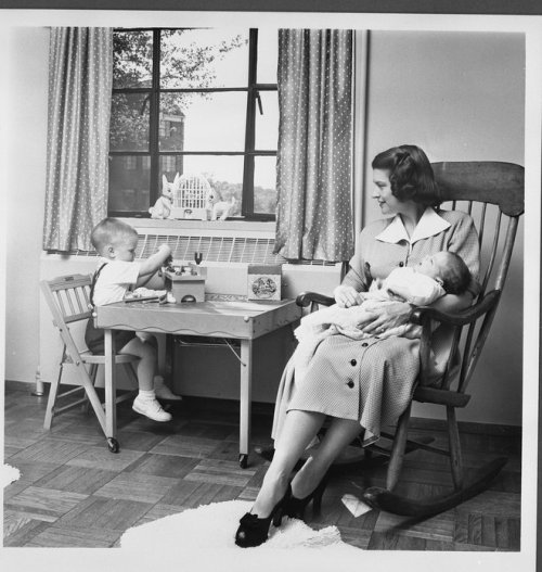 Betty's family in the Fifties Betty Ford holding infant Jack in her arms while Michael plays at a small table in their apartment.  1952.
