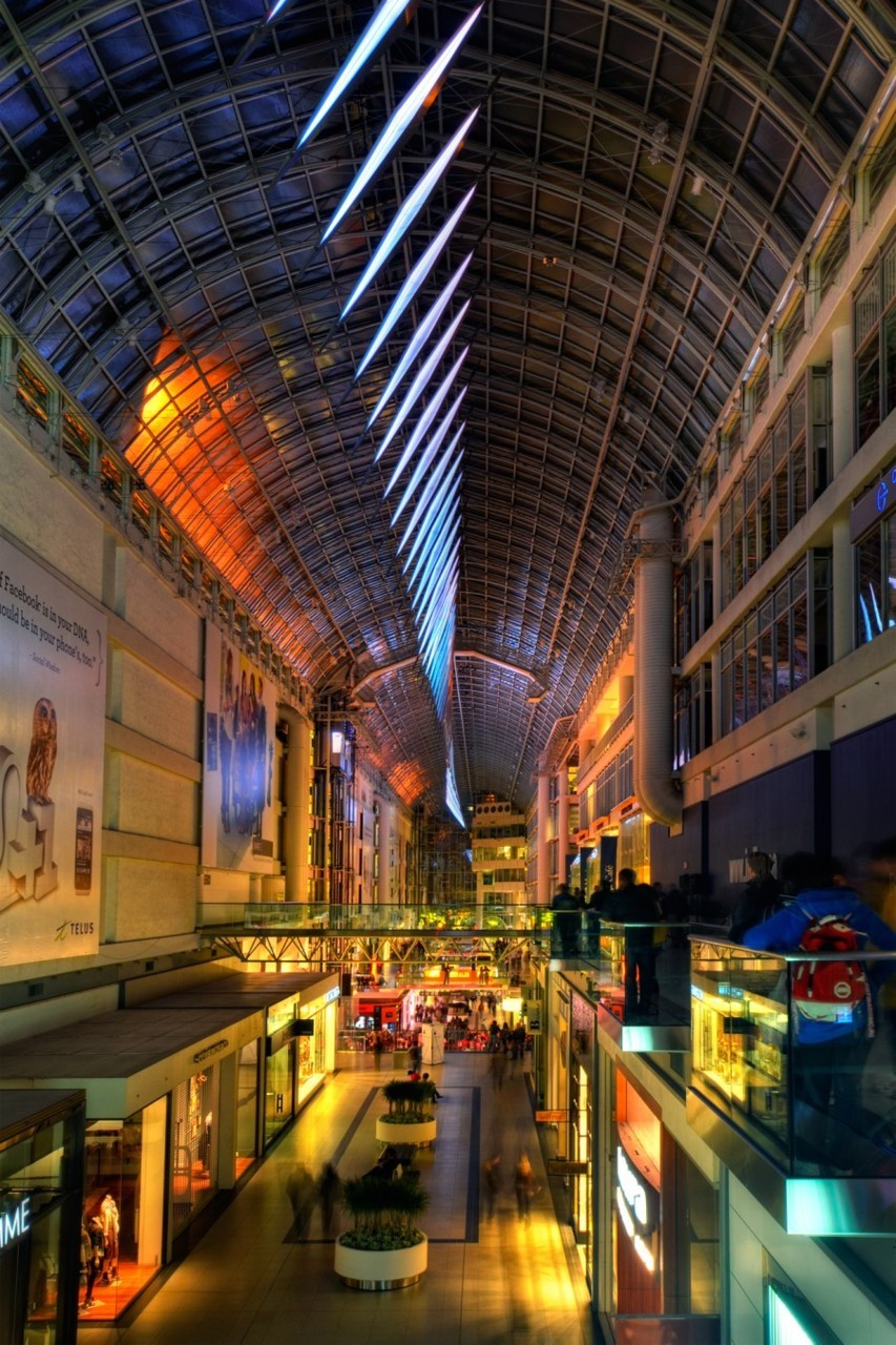 "New Toronto Eaton's Centre public display — ""Slipstream"" costs $2.5 million. Unveiled on October 1, 2011 as a part of Nuit Blanche celebration.  The 135m long LED light installation of 70 prisms is now joined the landmark Michael Snow Canada Geese.  Each prism is rotated by one degree to create a single gesture of motion. The animation of Slipstream changes in response to the movement of the sun throughout the day and local meteorological factors, such as wind speed. At night, as light animates from within, a momentum is created as impulses of light shift and stream throughout.  More photos from Nuit Blanche 2011"