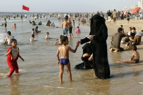 Rare groups of shy women in long flannel dresses enter the sea holding  children by the hand; their long skirts and colorful hijabs immediately  soak up salty water, like sponges. Bikinis? There are almost none.