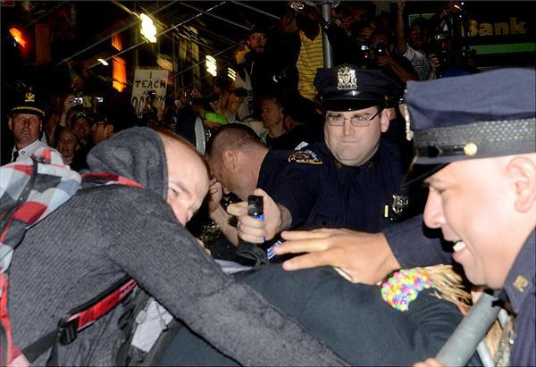 Cop pepper spraying a protestor.