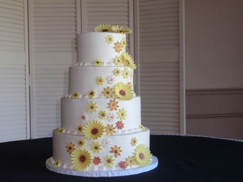 Hand made gumpaste daisys on a four tiered wedding cake. Cake by Cherry Lane Custom Cakes.