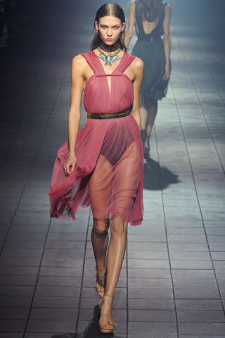 "Lanvin Spring RTW 2012 Paris Fashion Week Model: Karlie Kloss  (Paraphrased from Style.com) Designer Alber Elbaz insists that, by the time he's subjected it to his design process, there is almost nothing recognizable left of the story with which he starts each new collection. Before the show, he mentioned he had in mind an angel in hell, but as he drew and drew, the angel returned to earth.  This might have been the collection where Elbaz truly embraced sex. It was a major contributor to the strength of the show, along with those shoulders, which he was quick to point out had nothing to do with eighties padded power dressing. ""Power you can buy in a bank,"" he said. ""I prefer strength."" Against which he paraded sheer tulle dresses that conveyed a nothing-to-hide vulnerability."
