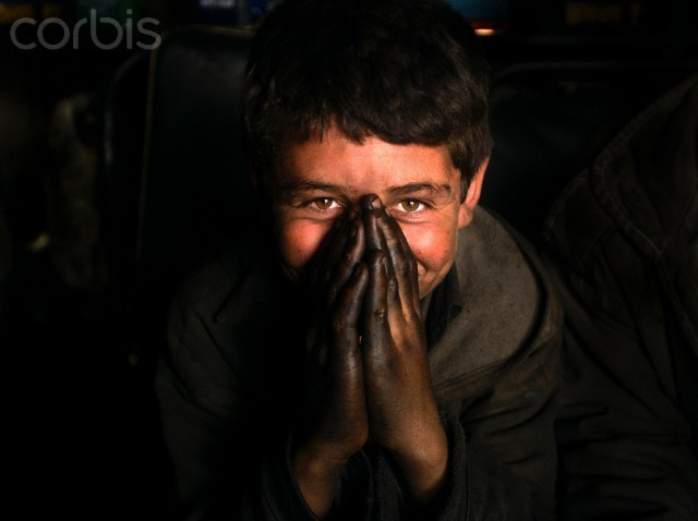 Weasdeen, 12, hides a smile behind his hands at an auto mechanic shop in  Kabul February 19, 2002.. He has been working for one year.  It is not  uncommon for Afghan children as young as five to be working full time.  Approximately 90 percent of children in Afghanistan do not go to school.  There were 28, 000 children working in the streets of Kabul in 1995,  50,000 in 1999, and estimated to be even higher today.