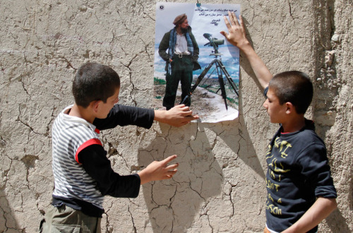 Afghan boys paste a poster of Afghan national hero  Ahmad Shah Massoud on a wall in Panjshir province. At  the entrance to Afghanistan's magnificent Panjshir Valley, an  84-year-old supporter of Ahmad Shah Massoud said his village was fully  armed to fight a resurgent Taliban to the end. September 7th, 2011.