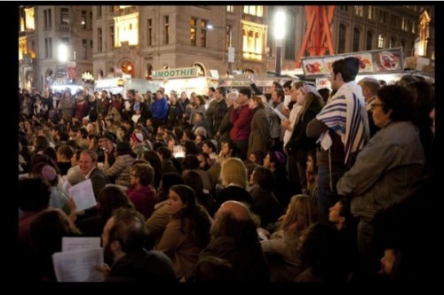 whatpath:    1,000 Jews gather at Wall St. for #occupy-yomkippur Kol Nidre   When new media activist Daniel Sieradski, a.k.a. the Orthodox Anarchist, a.k.a. @mobius1ski , suggested having an ad hoc Kol Nidre minyan on Wall Street, in solidarity with the Occupied Wall Street movement,  he wondered if he would succeed in attracting 20 participants (an  egalitarian minyan of 10 men and 10 women). To his amazement, over 1,000 Jews of all ages and backgrounds, from  secular to observant, showed up for an exhilarating experience which,  judging from the tweets (hashtag: #OccupyYomKippur), had many people  feeling as though they were practically levitating. Several friends told  me it was an incredibly moving experience. And in the supplemental confession of sins, they added the sin of not defending Palestine.