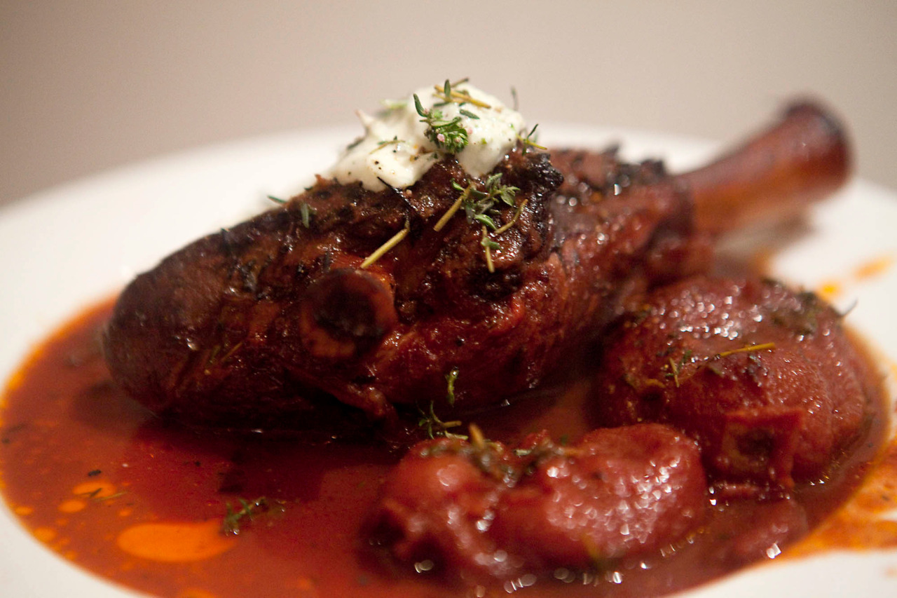 Red Wine and Tomato Lamb Shanks It took five minutes to put this together, and 2 hours to cook.  One of the better versions of lamb I've made, especially considering the effort put in. Ingredients: 2 lamb shanks, rubbed with salt 1 large can of whole roma tomatoes 1 cup of red wine 1/4 cup chopped thyme Salt, pepper and olive oil Put a few tablespoons of olive oil in an oven-proof baking dish on the stove.  Brown the lamb shanks for 3 minutes on each side, and then dump in the tomatoes, red wine, and top with thyme.  Season with salt and pepper, and put in the oven for 1.5 hours at 250C / 425F with the lid on.  Lower to 180C / 350F and remove lid for a half hour.  Serve with tzatziki and salad.